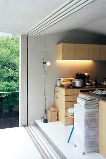 Small Space Live/Work Box Home in Japan - Photo 7 of 11 - Custom-made paulownia cabinets and a roomy balcony keep the compact second-floor living-dining-kitchen area from feeling cramped or cluttered.