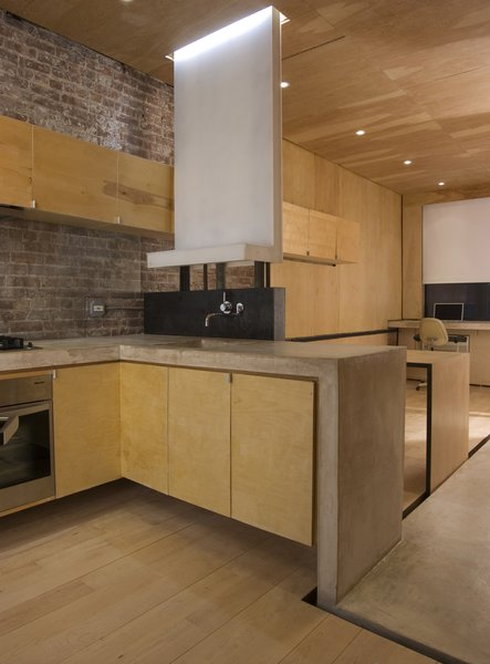 "The apartment, measuring just over 400 square feet, opens into the kitchen, which architectural designer Alan Y. L. Chan outfitted with a Dornbracht faucet and a sink of his own design. The black steel backsplash doubles as the back of a built-in bench on the other side. A concrete ""ribbon"" serves as the main design concept and the countertop, and continues throughout the apartment. A built-in LG refrigerator is located just across the concrete floor at right. Image courtesy Brian Riley."