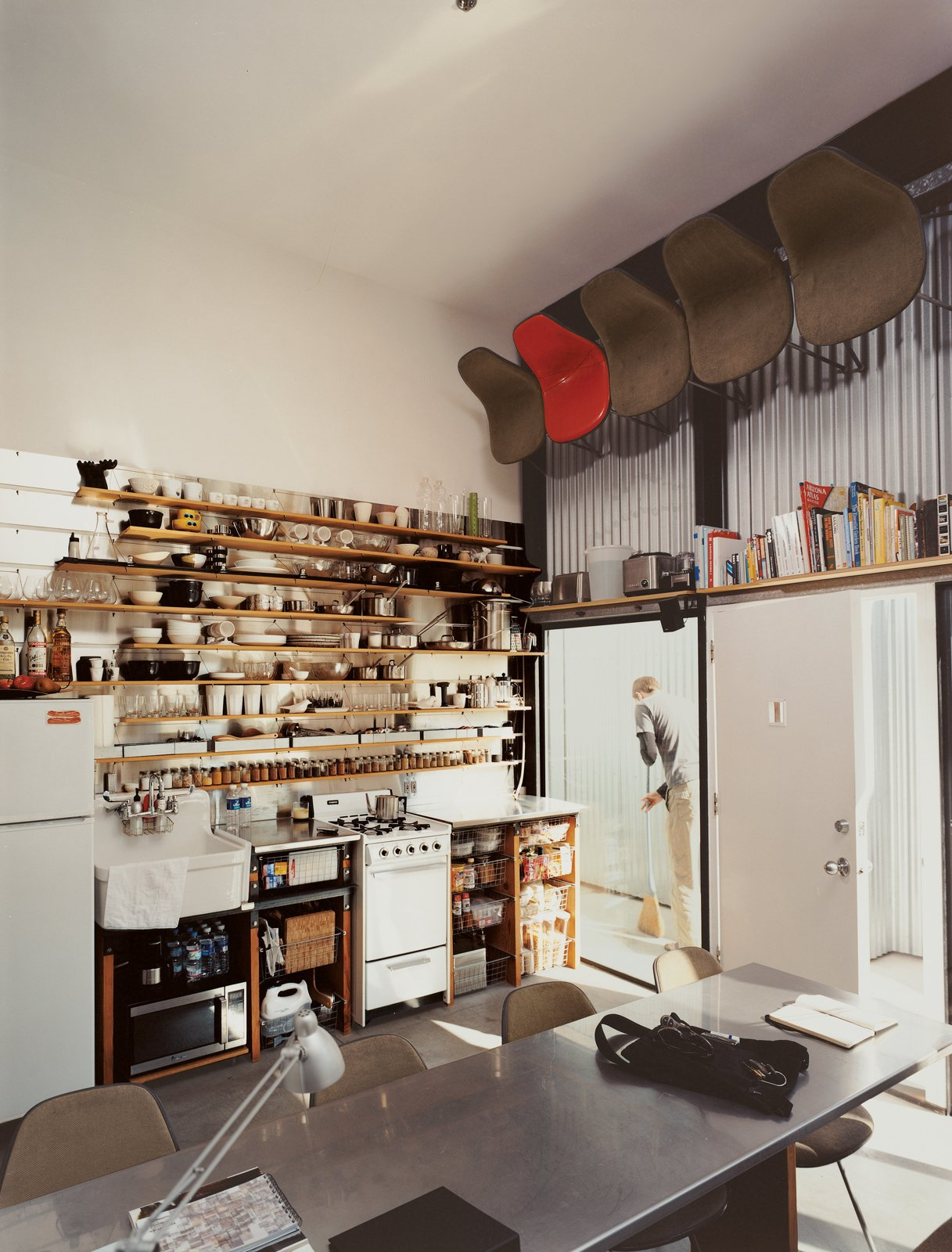 "The computer-designed kitchen area has the feel of a ship's galley, with everything neatly stowed, yet visible and instantly at hand: It's much the definition of ""ship-shape."" For dinner parties, well-worn Eames shell chairs are pulled down by David, with the help of a footstool. ""I have nearly an eight-foot reach,"" says the 6'3'' David. (""It gets a little tough if I have to spend a weekend or so alone,"" says Im.) Tagged: Kitchen and Wood Cabinet.  One-Room Wonders by Luke Hopping from Modern Mixed Use in San Diego"