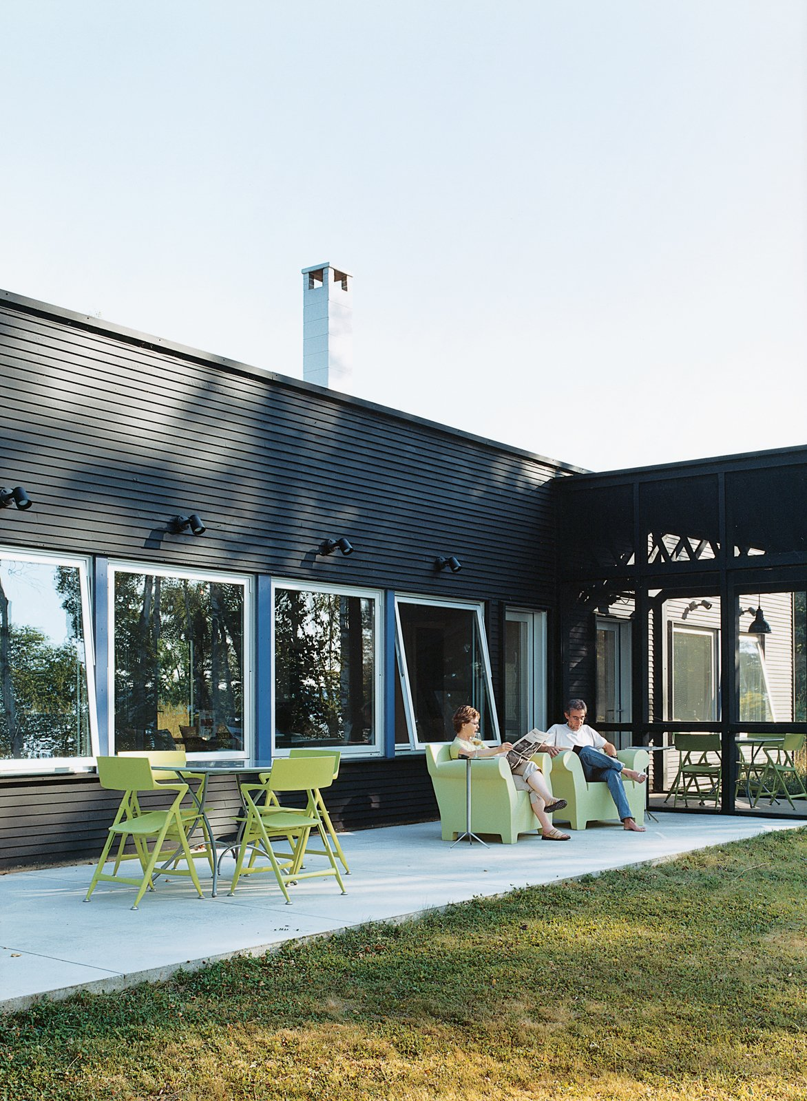 "The homeowners were impressed by the way Salmela conflated the indoor/outdoor continuum. ""We really needed that contact with the lake and the woods even when inside,"" says Golob. All outdoor seating by Kartell. Tagged: Outdoor, Grass, Concrete Patio, Porch, Deck, and Large Patio, Porch, Deck.  Striking Designs in Wisconsin by William Lamb from Off the Beaten Path"