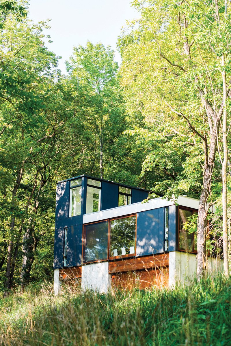 Set in the lush Wisconsin forest, this neatly stacked cabin was built vertically in order to minimize the amount of grading and landscaping necessary for construction. Photo by: Narayan Mahon Tagged: Exterior and Cabin Building Type.  Photo 6 of 101 in 101 Best Modern Cabins from Striking Designs in Wisconsin