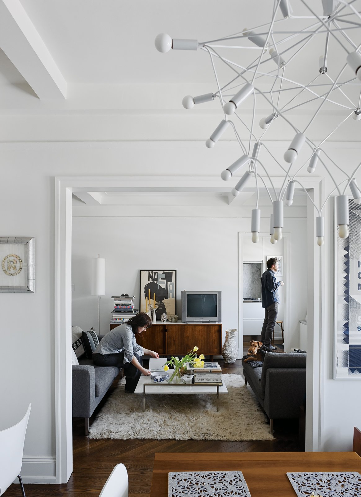 Up on the ninth floor, their sober Neo sofa and chaise from DWR and classic Florence Knoll credenza are contrasted by more exotic accessories like Patrick Townsend's Orbit chandelier and an offbeat white vase from Creative Growth, an Oakland, California, workshop for disabled artists. Tagged: Living Room, Sofa, and Coffee Tables. Creative Renovation in Brooklyn - Photo 2 of 13