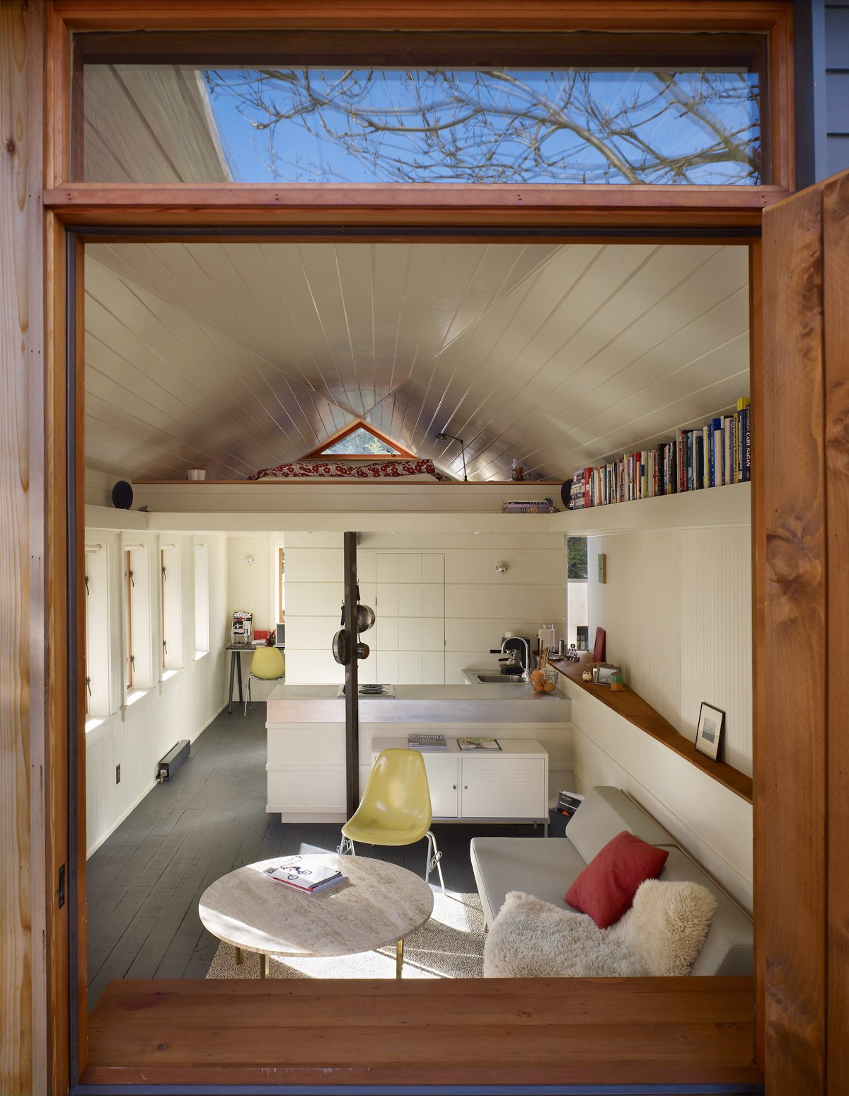 """Light cascades into the living room through a row of six insulated timber windows on the south wall. The north wall flares out to create what Schaer calls a sunset scoop. """"It grabs the late afternoon and evening sun and brings it deep into the space,"""" he explains."""