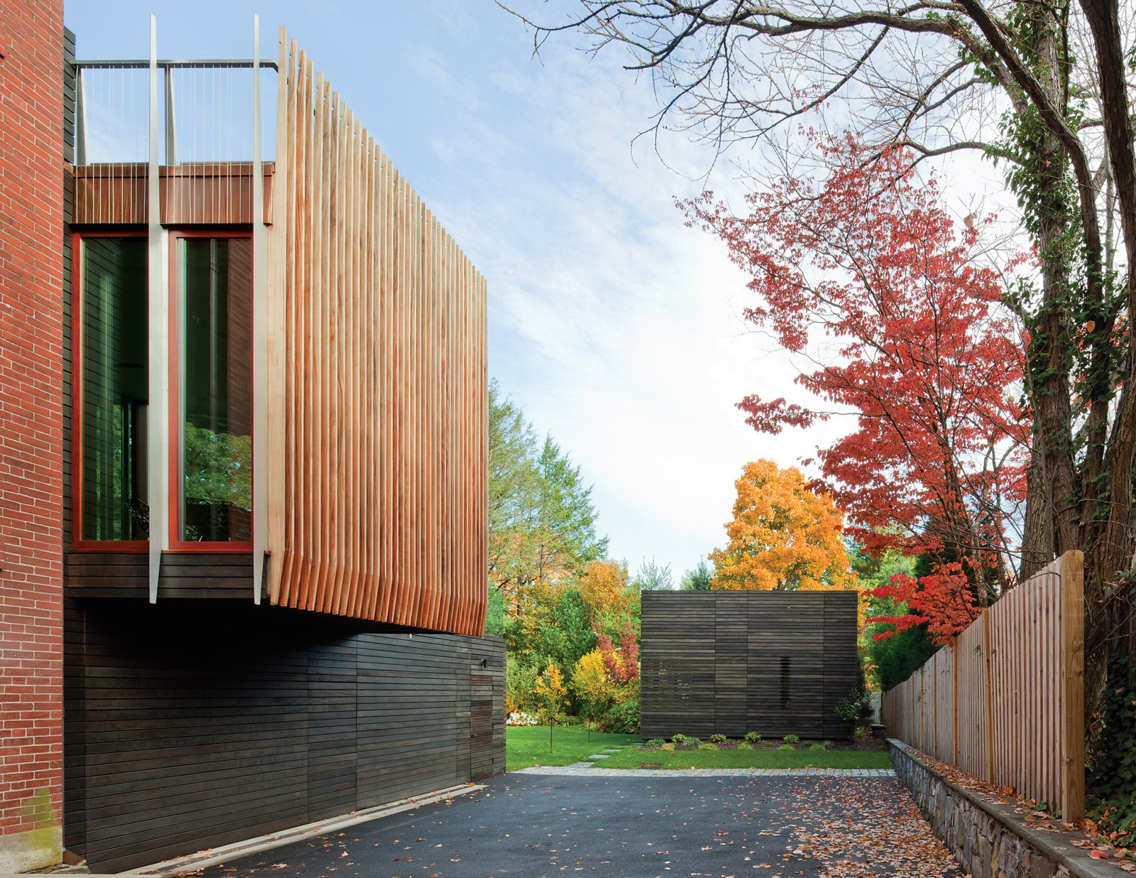 """Architecture firm NADAAA planned a striated addition to a brick neo-Georgian house in Boston with the owners' primary goal in mind: to engage with the outdoors year-round. The walls of the rear kitchen and living space are virtually all glass, allowing sight lines to the existing gardens and new pool house through a series of framed vignettes onto the backyard landscape. The glass box is bookended by uniform """"fins"""" that mark the edge of each picture window, as shown here. Photo by John Horner."""