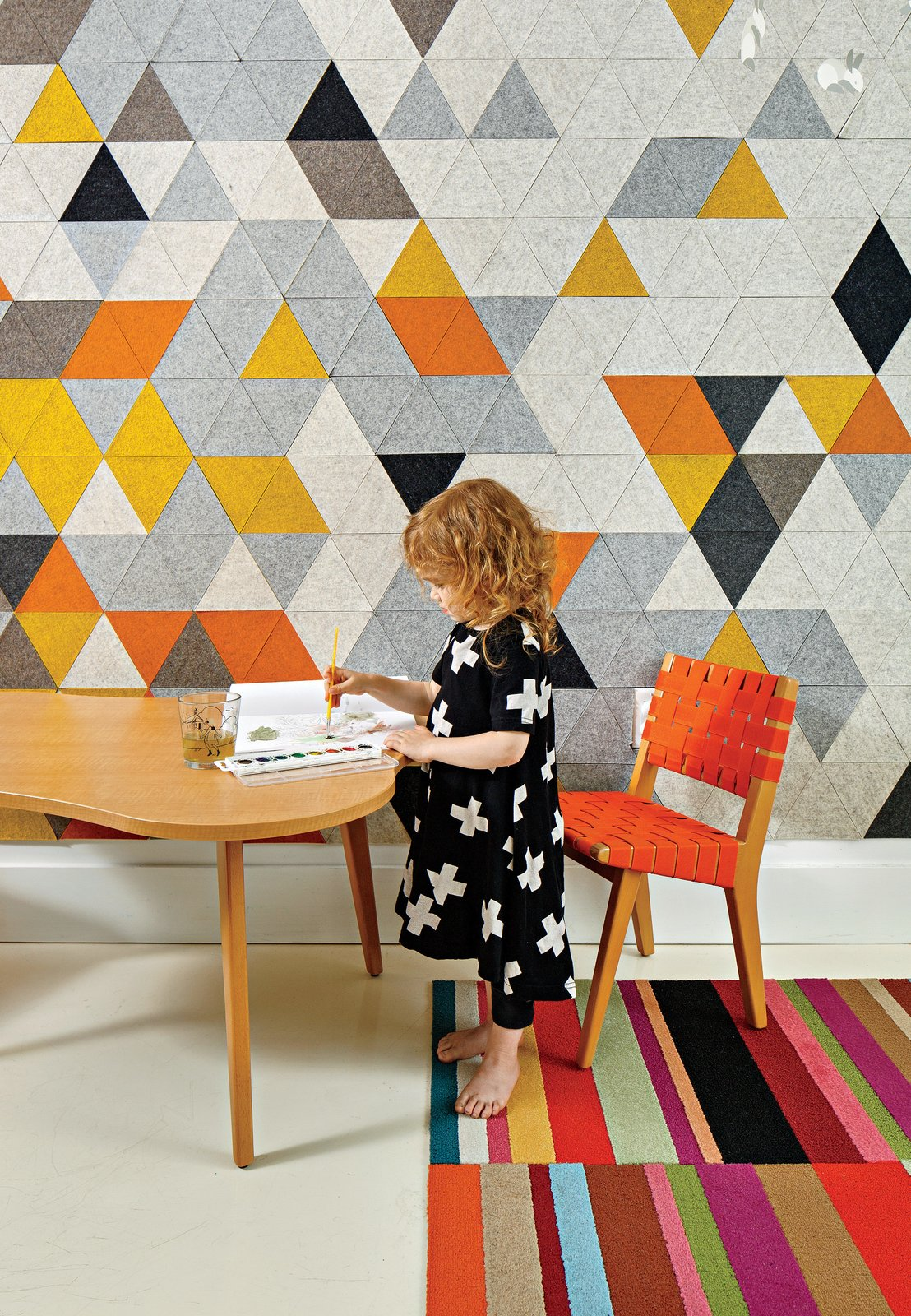 Chris Grimley and Kelly Smith transformed a cramped apartment into a family-friendly home. The room shared by Mae, three, and her little brother Roen, one, features a custom prototype mural by FilzFelt, their mother's textile design company. The carpet is by Flor, and the child-size chair and Amoeba table are both by Jens Risom for Knoll. Tagged: Kids Room, Playroom, Chair, Desk, and Rug Floor.  Photo 1 of 8 in Boston Renovation Accents Minimalist White with Rich Felt Murals