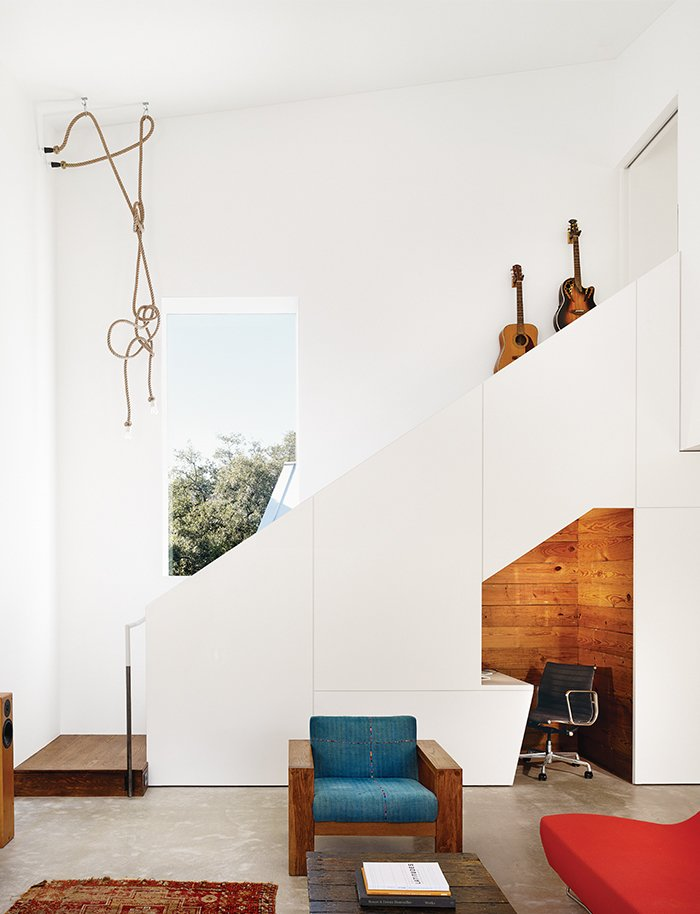 Sam Shah and Anne Suttles asked architect Kevin Alter to renovate their 1920s bungalow in Austin, Texas, and add an addition, which contains a living area downstairs and an office upstairs. They tucked an office nook under the stairs; the Eames chair is a hand-me-down from Shah's father.