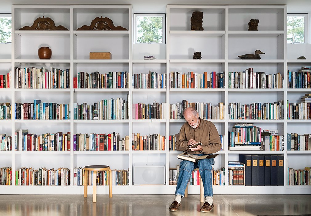 In the living area, Brothers sits on an Artek stool while perusing a selection from his library. Tagged: Living Room, Bookcase, Concrete Floor, and Stools.  Gigantic Home Libraries by William Harrison from Idyllic Home Designed for an Artist