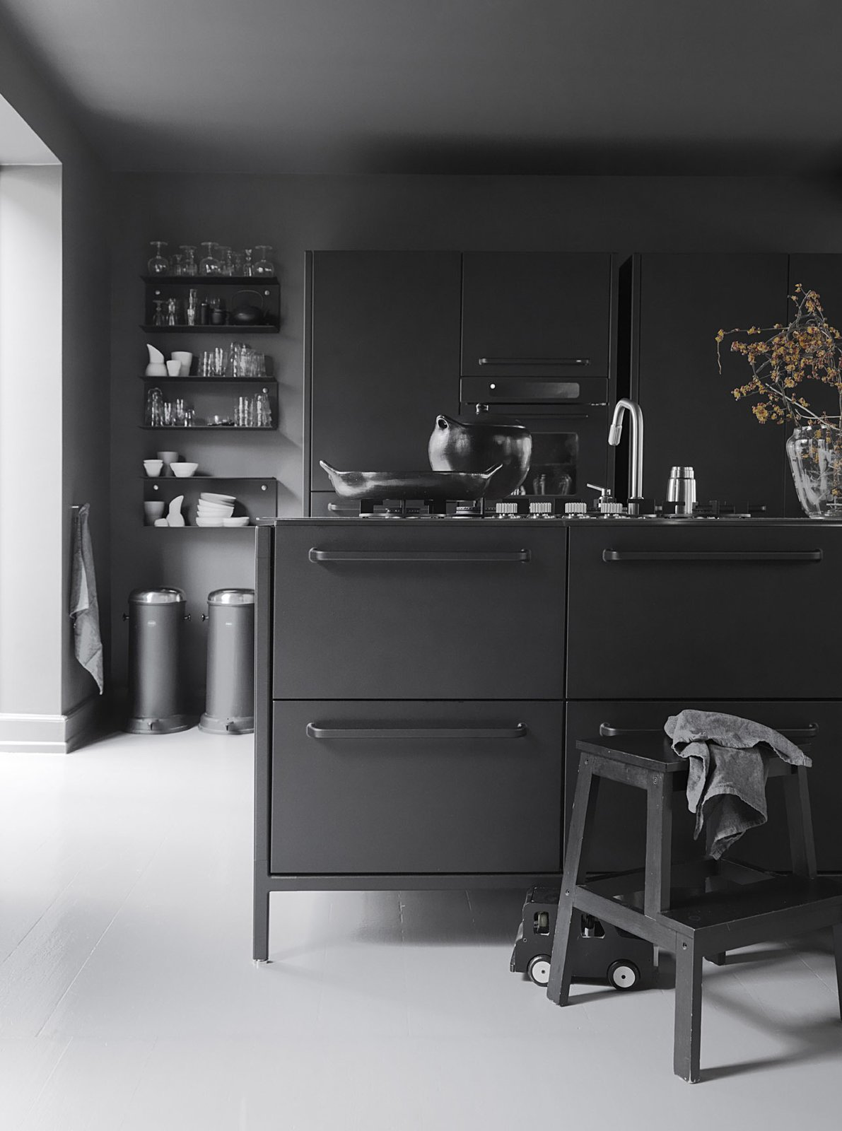 The iconic waste bin that gave Vipp its start is a mainstay in the Egelunds' home, as are many of the company's streamlined design solutions. The waste bins, shelves, glasses, and ceramics are by Vipp. Tagged: Kitchen and Painted Wood Floor.  Photo 6 of 11 in 10 Stunning Ways to Use Black in Your Kitchen from Black, White, and Gray All Over: Monochromatic Copenhagen Townhouse