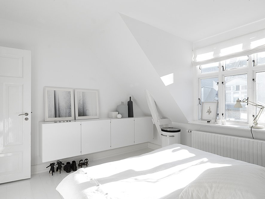 On the upper floors, bright white walls and plenty of natural light make the bedrooms and living rooms feel large and spacious. In the master bedroom, built-in cabinetry hides clutter. The art photography against the wall is by Anders Hviid, the bed is Hästens, the laundry basket is Vipp, and the lamp is Fontana Arte.  Modern Danish Homes We Love by Aileen Kwun from Black, White, and Gray All Over: Monochromatic Copenhagen Townhouse