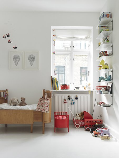 Even the children's rooms, though peppered with colorful details, retain the stark white walls and minimal feel of the rest of the Egelunds' home. The wooden bed is by Juno, the doll bed are by Flos Lampadina, and the shelves are Vipp.