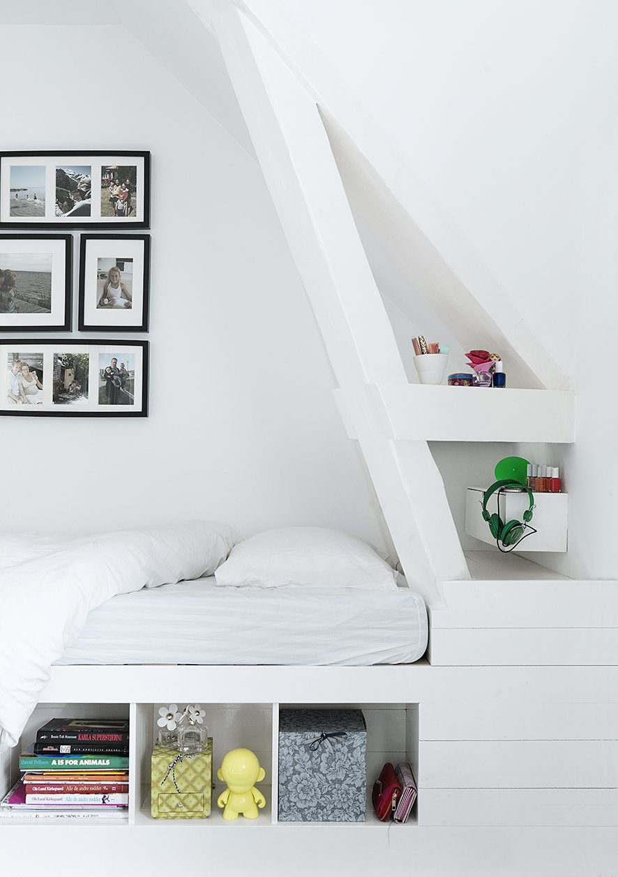 Custom details like this corner bed with built-in shelving keep the younger generation's spaces playful, but still sophisticated. With four children, utilizing space wisely became a top priority, and the family relies on custom shelving and built-ins to keep clutter at bay. The bed is custom with IKEA frames. Tagged: Bedroom, Bed, and Storage.  Bedrooms by Dwell from Black, White, and Gray All Over: Monochromatic Copenhagen Townhouse