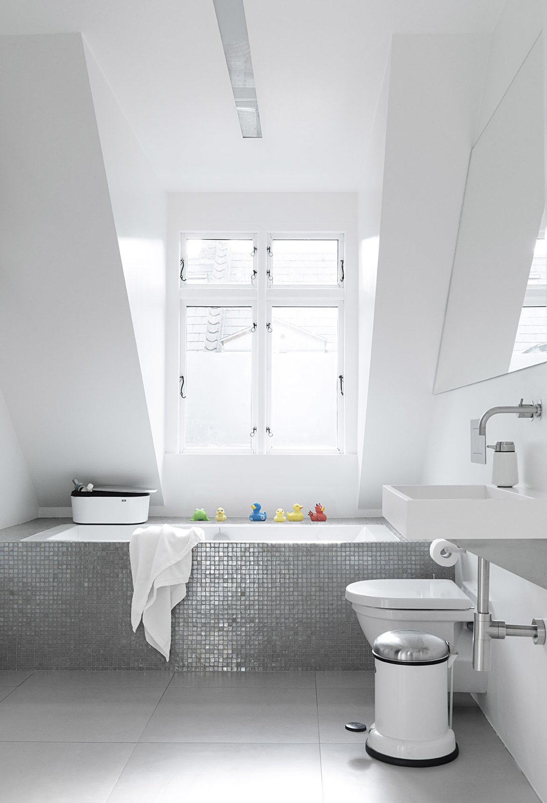 Sofie and Frank built a box around an ordinary glass fiber shell bathtub, then covered it in a mosaic of shower tiles. Natural light from a large dormer window gives the tiles an almost iridescent glow. The toilet is Duravit. Tagged: Bath Room, Drop In Tub, and Wall Mount Sink.  Photo 10 of 12 in Black, White, and Gray All Over: Monochromatic Copenhagen Townhouse