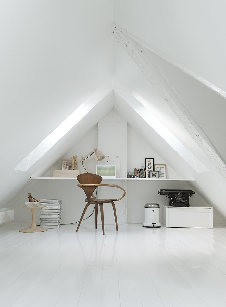 A vaulted loft room complete with a typewriter and natural wood furnishings serves as the perfect hidden workspace. The chair is a vintage Cherner chair, the side table is Nanna Ditzel, and the wood lamp is a Muuto Wood model.