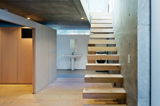 Open-Plan Concrete Home in Japan - Photo 2 of 7 - The staircase leads to the living area upstairs.