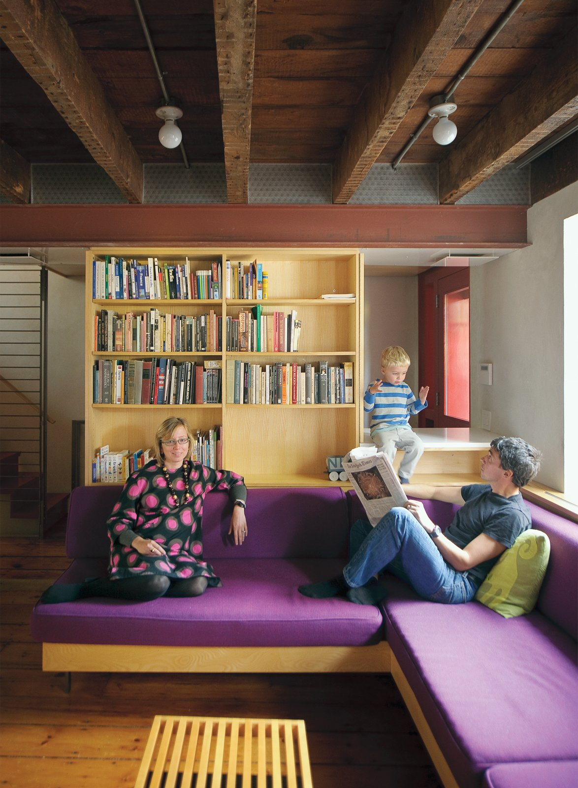 The exposed ceiling beams and inserted steel framing system are visible in the lower level, where Lange and Dixon relax with their son Paul.