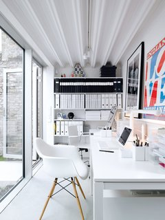 Contemporary Nordic Town House - Photo 8 of 14 - The office, which is a single-level separate unit, boasts Ikea desks and a signed work by Gilbert and George (friends of the couple).