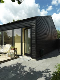 "30 All-Black Exterior Modern Homes - Photo 3 of 30 - Since Copenhagen is generally cold, the house was painted black to trap warmth. The result was that in its first year, it consumed so little energy that the client received a generous refund from the heating company. ""Many wooden houses in Scandinavia use this trick,"" Larsen says. ""On sunny days it even radiates warmth, so that in spring and autumn you can sit outside by the wall and in this way extend the outdoor season by a few weeks every year. These weeks are valuable in places with little light."""