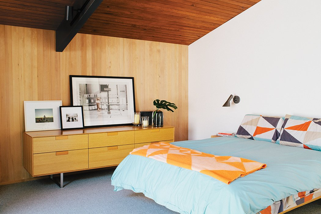 Arne Jacobsen's AJ Wall Lamps are in the master bedroom, which is furnished with a Case Study bed and a Series 11 6 Drawer Console by Blu Dot. Tagged: Bedroom, Bed, and Dresser.  Blu Dot Spotted by Blu Dot from Midcentury Renovation in Portland Capitalizes on Nature with Seven Doors to the Outside