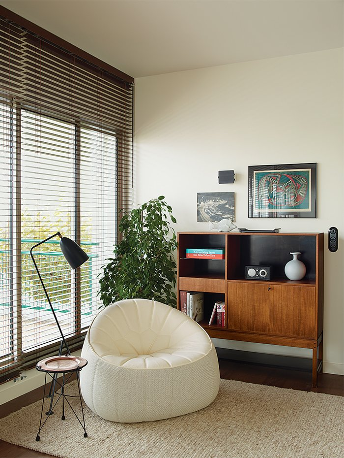 A Noé Duchaufour-Lawrance chair, Charlotte Perriand wall sconce, and Greta Grossman Grasshopper floor lamp round out a corner in the living room. Deau made the side table herself. Tagged: Office, Study, Chair, Bookcase, Storage, Lamps, and Rug Floor.  Best Photos from Modern Home Furnished With Flea Market Finds