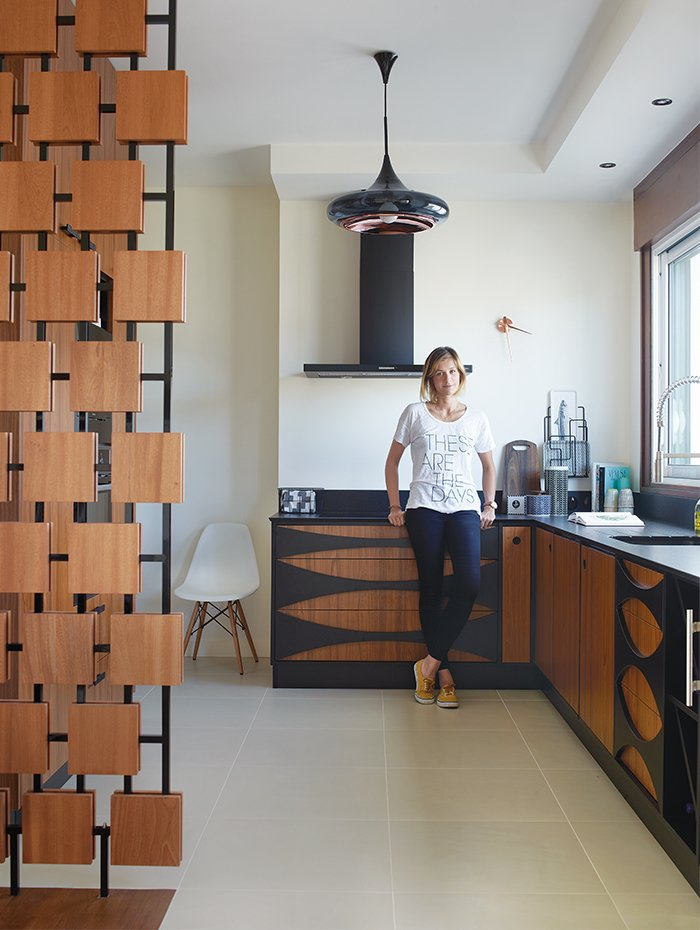 In the renovation of a 1950s building in Royan, France, interior designer Florence Deau selected a fleet of vintage and new furnishings. Tagged: Kitchen, Ceramic Tile Floor, Wood Cabinet, and Pendant Lighting.  Photo 3 of 10 in 10 Modern Renovations to Unique Homes in France from Editor's Picks: 4 Modern Interiors We Love