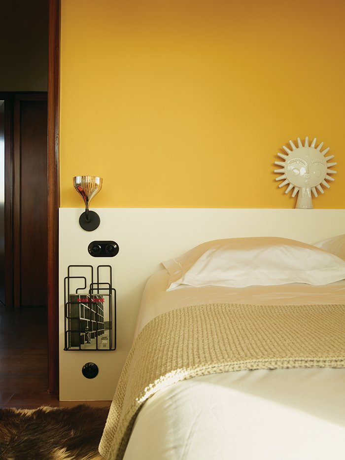Farrow & Ball's Babouche yellow enlivens one of the bedrooms. Tagged: Bedroom, Bed, and Wall Lighting.  Photo 22 of 25 in 25 Bold Ways to Decorate with Yellow from Modern Home Furnished With Flea Market Finds