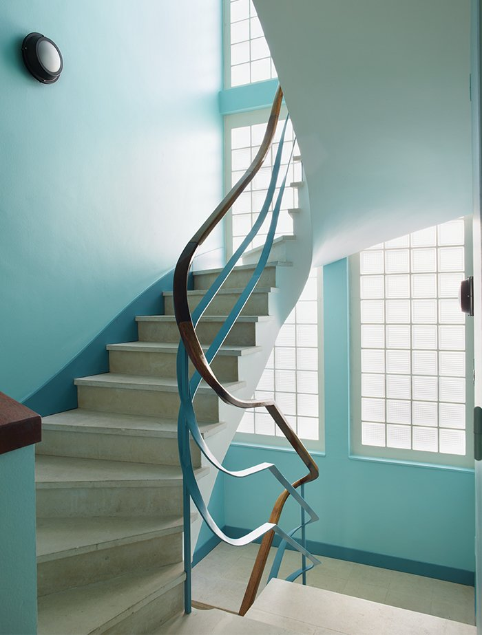 The apartment can be reached by a winding staircase. Tagged: Staircase, Metal Tread, and Wood Railing.  Photo 10 of 17 in Modern Home Furnished With Flea Market Finds