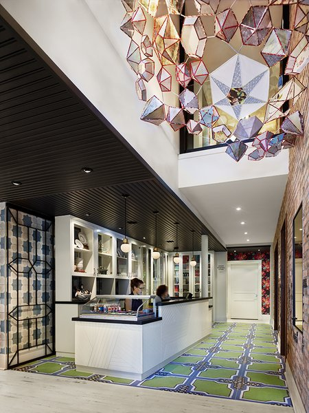 An installation by Kirsten Hassenfeld hangs above the custom reception desk, which is topped with slate. The floor tiles are 14OraItaliana's iGattipardi line. &Tradition makes the pendant lights and the Vivid Victorian wallpaper is from Flavor Paper.