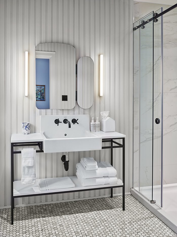 The spa-like bathroom features marble tile and a freestanding vanity. Tagged: Bath Room, Pedestal Sink, Wall Lighting, Enclosed Shower, and Porcelain Tile Floor.  Photo 7 of 7 in Modern Boutique Hotel in a 19th-Century Foundry