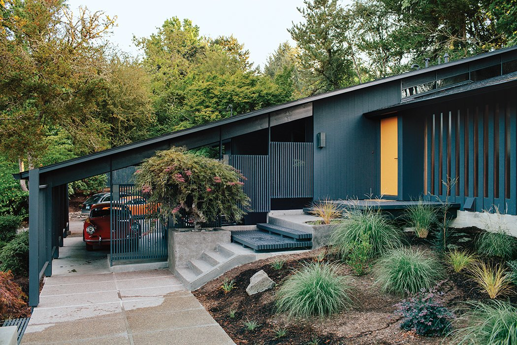 Jessica Helgerson Interior Design, with project manager and lead designer Emily Kudsen Leland at the helm, remade a Portland abode with a crisp paint palette: Benjamin Moore's Wrought Iron for the cladding and Venetian Gold for the front door. Landscape design is by Lilyvilla Gardens. Tagged: Exterior, House, Wood Siding Material, Mid-Century Building Type, and Shed RoofLine.  Mid Century Modern by Katt Lewis from Midcentury Renovation in Portland Capitalizes on Nature with Seven Doors to the Outside
