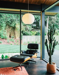 Doughnuts, Menswear, Chicken Sandwiches and Dwell - Photo 1 of 1 - In true mid-century fashion, a George Nelson Bubble Lamp is paired with an Eames Lounge by Charles and Ray Eames in a corner of the living room. The glass walls and mitered corner are original features of architect Saul Zaik's 1956 design.
