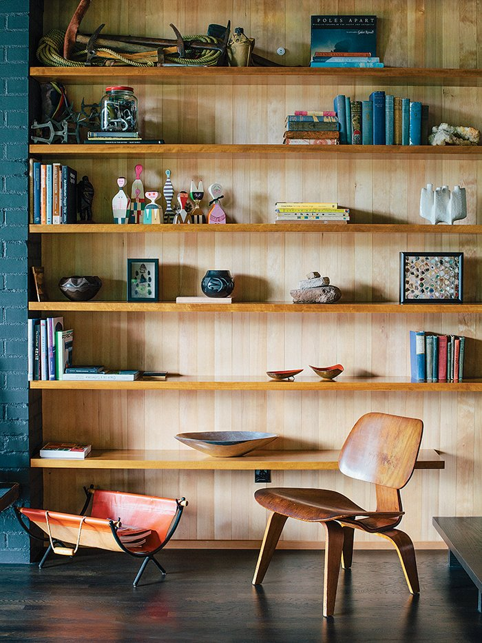 A vintage Molded Plywood Lounge Chair (LCW) by Charles and Ray Eames for Herman Miller sits in front of built-in shelving in untreated hemlock. Tagged: Storage Room and Shelves Storage Type.  Photo 5 of 19 in Midcentury Renovation in Portland Capitalizes on Nature with Seven Doors to the Outside