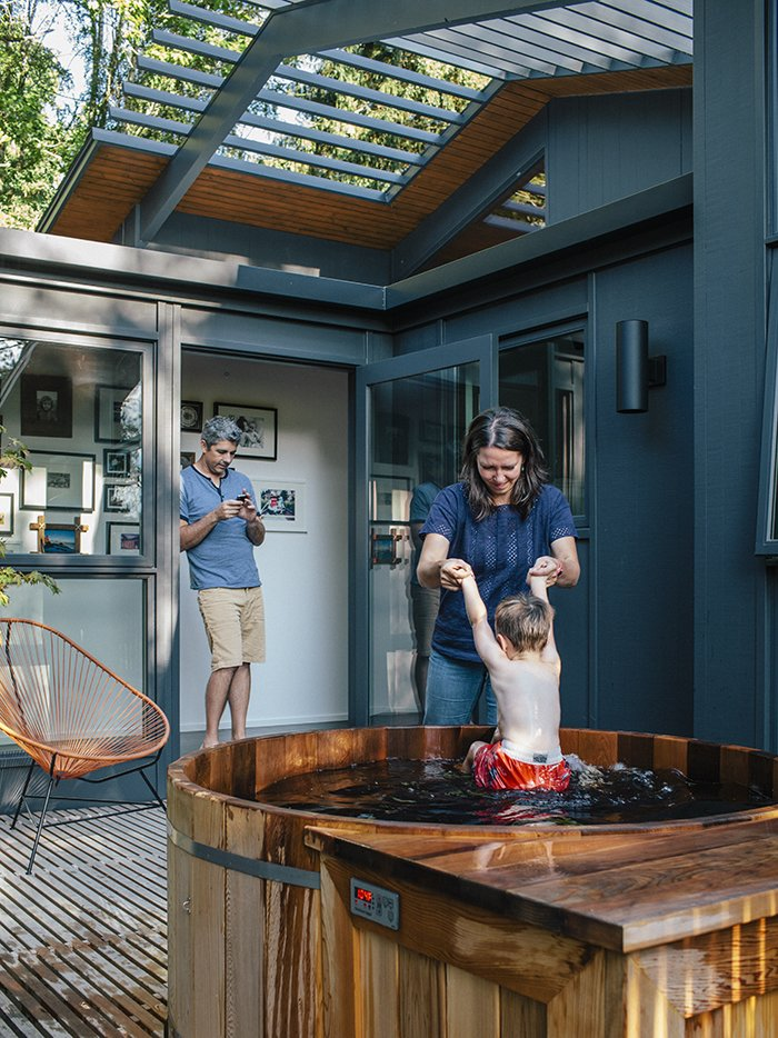 Kelly Milford helps son Adam out of the hot tub nestled on a wood deck in back of the house. The exterior paint is Wrought Iron by Benjamin Moore. Midcentury Renovation in Portland Capitalizes on Nature with Seven Doors to the Outside - Photo 16 of 19