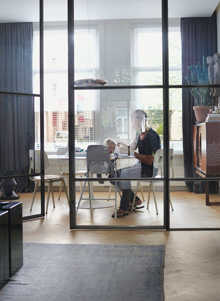 Nederhof and his son Scott sit at a Tulip table by Eero Saarinen for Knoll in the flexible office area. The chairs are by Friso Kramer for Ahrend, and the Corona pendant light is from Established & Sons.  Photo 2 of 6 in A Restless Real Estate Developer Builds His Ideal Live-Work Space