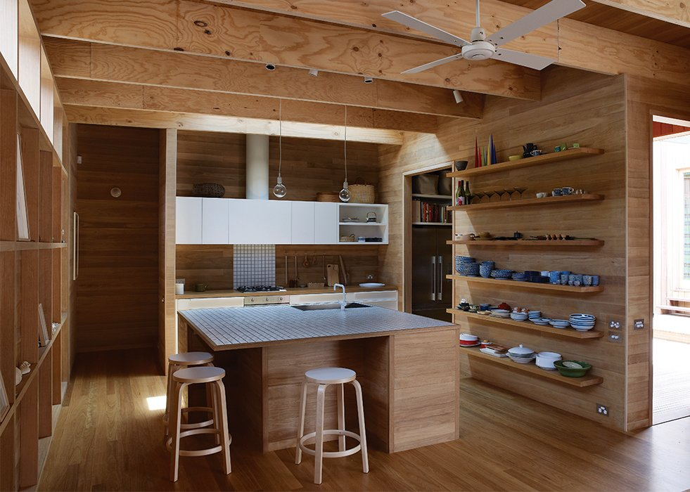 The almost-entirely tallowwood kitchen is custom. Muuto pendant lights, bar stools by Alvar Aalto for Artek, a Vola faucet, and a ceiling fan by Beacon Lighting finish the room.