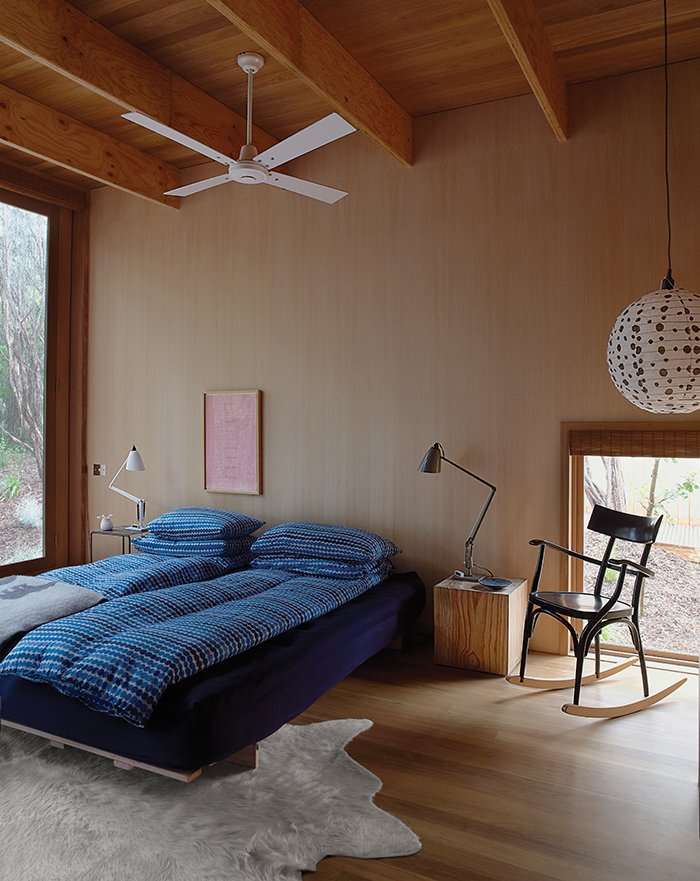 In the master bedroom, the rocking chair is by Thonet and the bespoke rug is by Armadillo & Co. Tagged: Bedroom, Bed, Lamps, Table Lighting, Pendant Lighting, Light Hardwood Floor, Night Stands, and Rug Floor.  Bedrooms by Dwell from Local Wood Clads Every Surface of This Idyllic Australian Getaway
