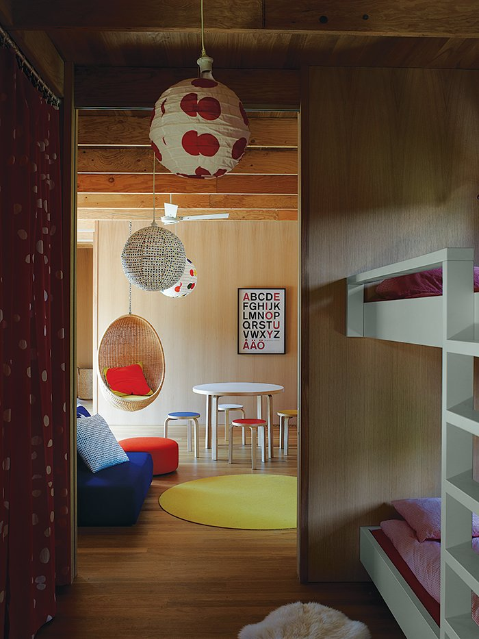 The couple's ten-year-old twins have connecting rooms next to a play space furnished with Aalto stools, a table from Artek, and a Nanna Ditzel rattan hanging chair purchased at Interstudio. Tagged: Kids Room and Playroom. Local Wood Clads Every Surface of This Idyllic Australian Getaway - Photo 7 of 9