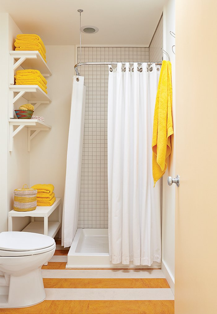 In the guest bathroom, a set of Senegalese nesting baskets mirrors the yellow-and-white pattern on the linoleum floor. 25 Bold Ways to Decorate with Yellow - Photo 14 of 25