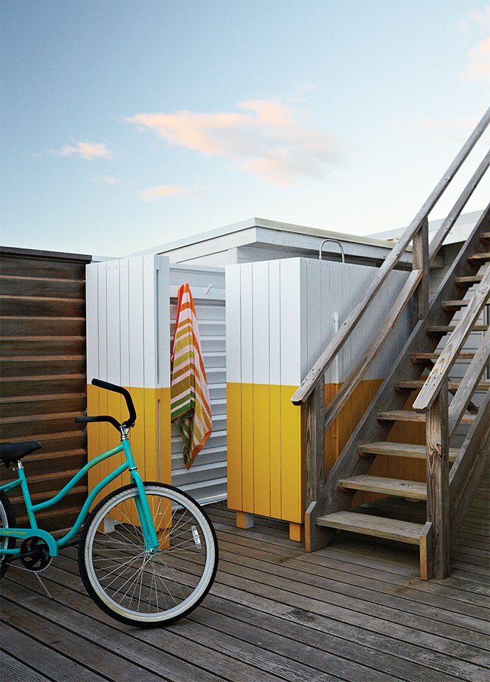 The wood screen concealing the outdoor shower was painted yellow and white, matching the color scheme in the guest bathroom. These 13 Outdoor Showers Will Make You Consider One For Your Own Yard - Photo 3 of 14
