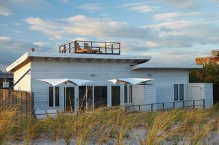 9 Modern Beach Bungalows - Photo 1 of 9 - A small beach retreat originally dating from the 1950s on Fire Island, New York, was revamped by interior designer Alexandra Angle. With a location high on a hill overlooking the water, an outdoor roof terrace and patio help bring the outdoors in.