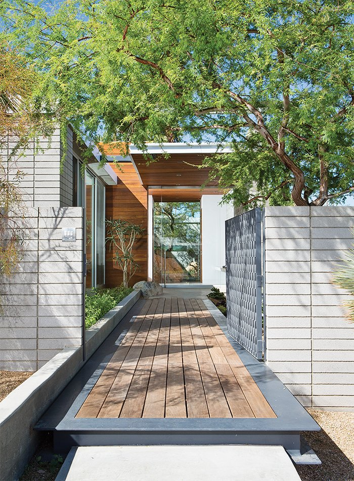 An ipe walkway leads past a steel gate to the guesthouse. Vacation Home in the California Desert is a Modernist Oasis - Photo 2 of 12