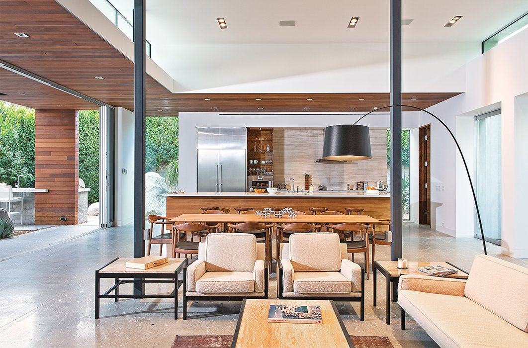 Custom walnut and stainless steel sheathes the kitchen, which is open to the living-dining area and the patio. The Twiggy lamp is by Foscarini; the sliding doors are from Fleetwood.