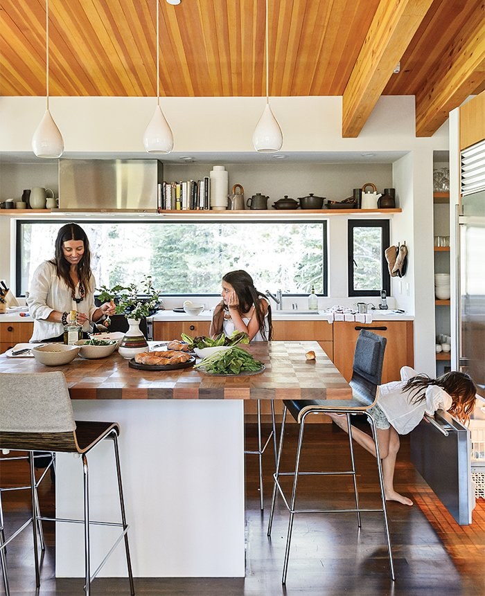 In the kitchen, designer Maca Huneeus prepares lunch with her daughters Ema, 12, and Ofelia, 7. The pendants are Jonathan Adler; the island is a custom design, inspired by a 1960s Dansk tray that belonged to Huneeus's mother. The barstools are from Blu Dot. Tagged: Kitchen, Dark Hardwood Floor, Pendant Lighting, and Refrigerator.  Blu Dot Spotted by Blu Dot from How to Take a Dwell Photo