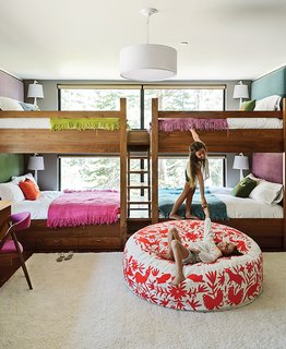 15 Modern and Creative Spaces For Kids - Photo 14 of 15 - In the kids' bunk room, Maca designed walnut beds with built-in storage and fabric headboards, and covered each one in hand-knit blankets by Marcela Rodriguez-Chile. The giraffe sconces are from Jonathan Adler. The girls play on a hand-embroidered Olli lounger from Heath Ceramics.