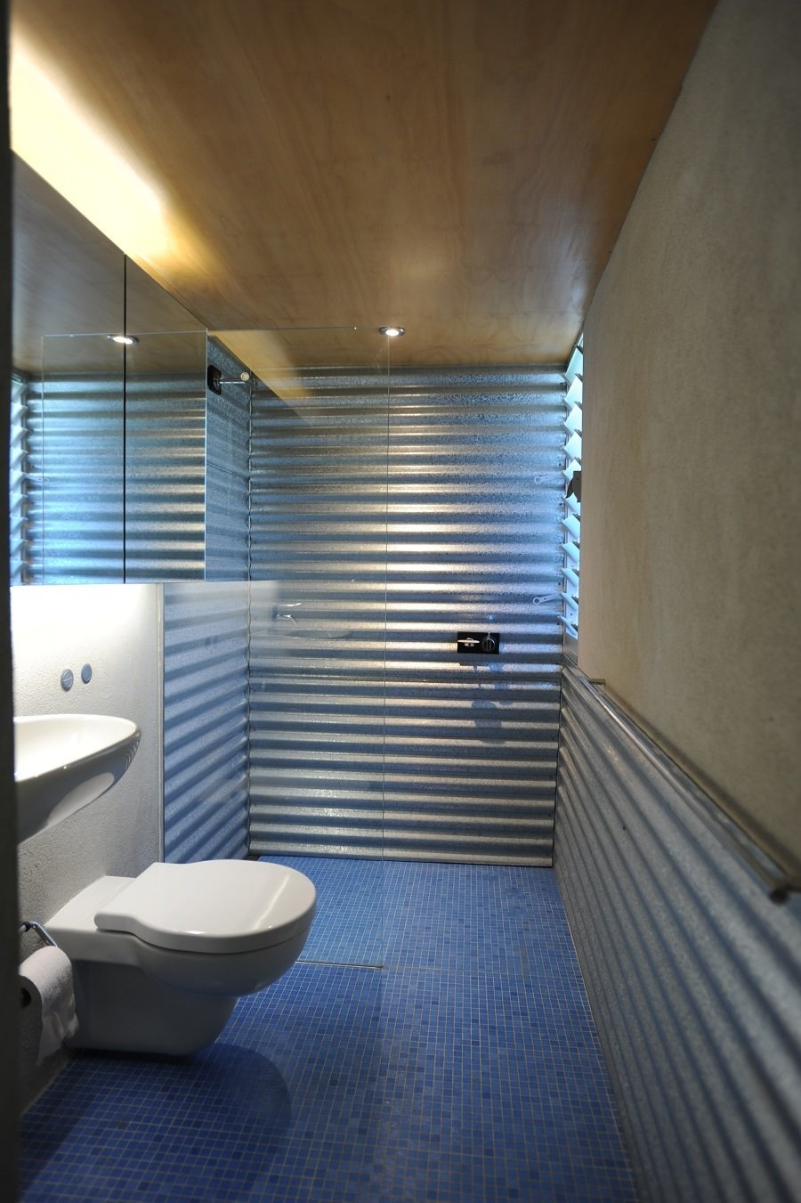 "The blue bathroom tiles were inspired by a ""Corbusian use of color,"" according to the architect, and take advantage of the lowered floor to create a metaphorical step into a pool. The corrugated metal continues throughout, even wrapping around the walls of the shower."