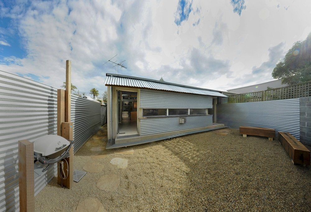 The architect reconfigured the house so the living space opens to the yard. He also took the exterior elements and used them to decorate the interior.  Photo 10 of 10 in Compact Australian Home Clad in Steel and Concrete