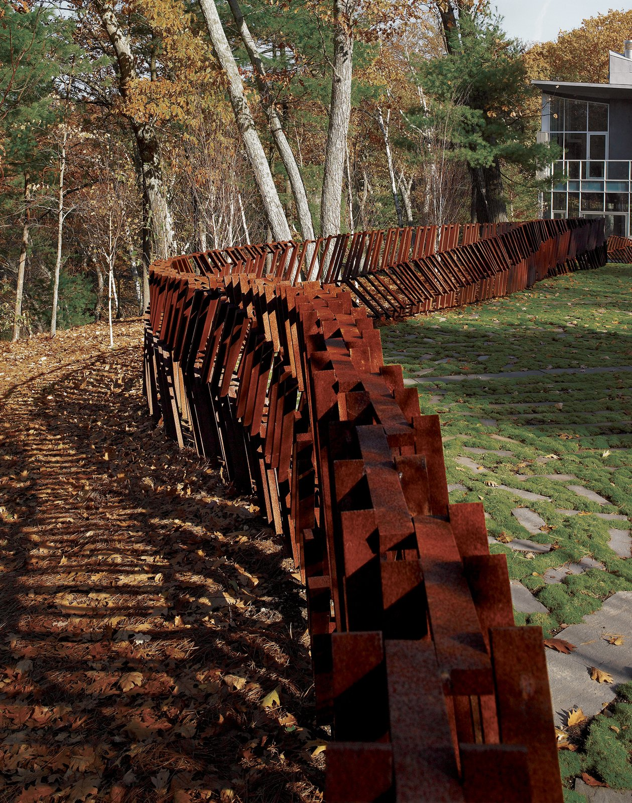 "Landscape architect and artist Mikyoung Kim created a Cor-ten steel fence to enclose a three-acre site in Lincoln, Massachusetts. ""The entire fence is made using just seven lengths of modular, precut Cor-Ten steel bars, with widths being anywhere from two to five bars thick,"" explains the designer. ""Depending on the angle from which you see it, the fence can appear transparent or opaque."" Read the full article here.  30+ Best Modern Fences by William Lamb from On the Fence"