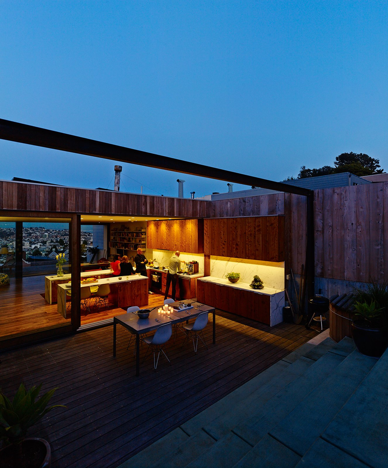 At night, opening the entire top floor is a breeze. Russell-Clarke and Moolsintong are even planning of rigging some kind of sail over the back patio for shade. The hot tub is by Roberts Hot Tubs. Tagged: Exterior, Wood Siding Material, and House.  Photo 15 of 17 in Striking Slatted Wood and Glass Home in San Francisco