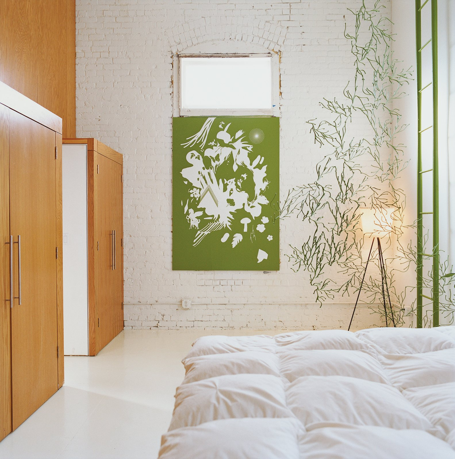 The bedroom is decorated minimally by another Vogt screenprint, and a strand of green Algue.  Photo 4 of 10 in A Minneapolis Building That Has Lived Multiple Lives Is Revitalized by a Coffeehouse Owner