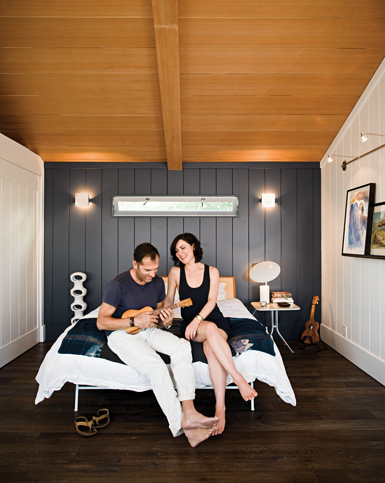 """There's a soulfulness in this small house that's impossible to replicate in something completely new. The sweetness truly lingers,"" says architect Michael Lee.  Tagged: Bedroom, Bed, and Dark Hardwood Floor.  Bedrooms by Dwell from Less is More in this Manhattan Beach Bungalow"