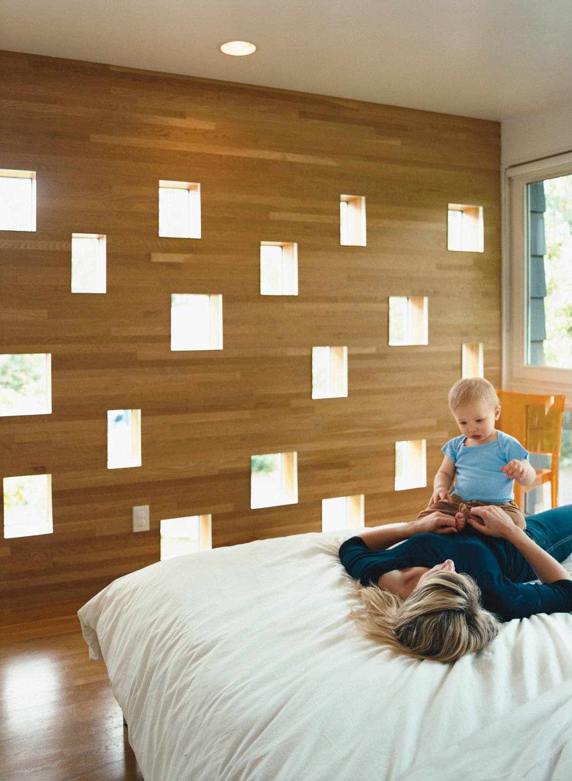 Karie and Mason enjoy a playful loll on the bed in the Deans' new master bedroom. The perforated wall facing the neighbors' backyard offers a great deal of diffuse light while still managing to conceal the Deans' boudoir from prying eyes.  Photo 2 of 9 in Minneapolis, MN